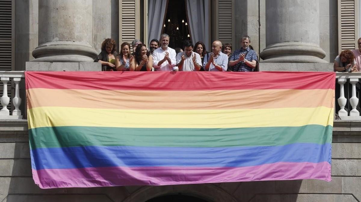 Representantes del Ayuntamiento de Barcelona, con la bandera gay que desde este martes cuelga del balcón principal del consistorio.