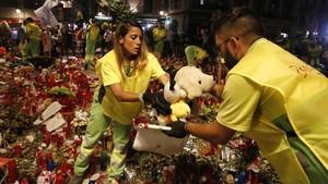 Trabajadores municipales retiran los objetos depositados por los ciudadanos en la Rambla en homenaje a las víctimas del atentado del 17 de agosto.