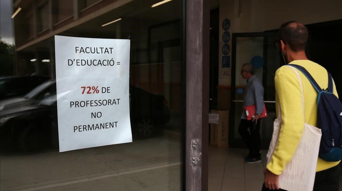 Un joven entra en la Facultat dEducació de la UB, junto a unos carteles reivindicativos.
