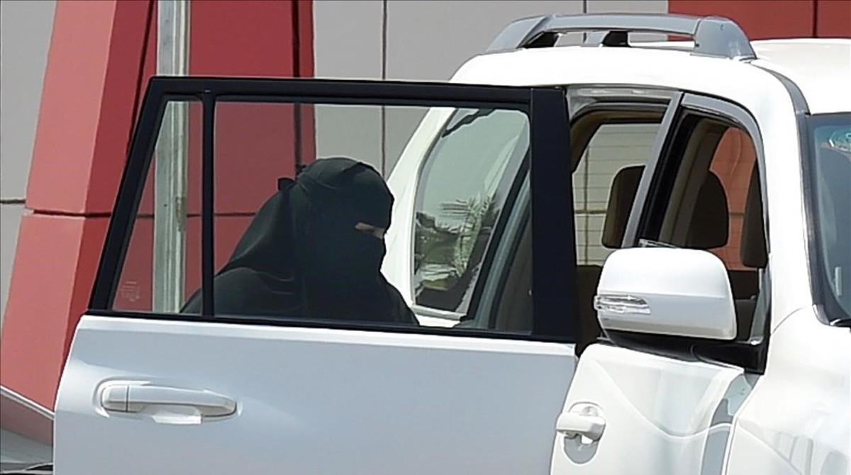 Una mujer entra en un coche en Riad.