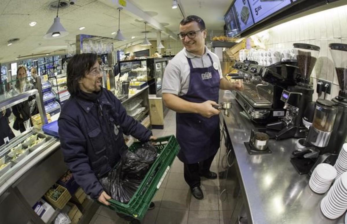 Iván recoge los residuos de café de uno de los locales de la estación de Sants gestionados por la empresa Areas.