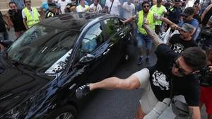 Un participante en la manifestación de taxistas da una patada a un cabify.
