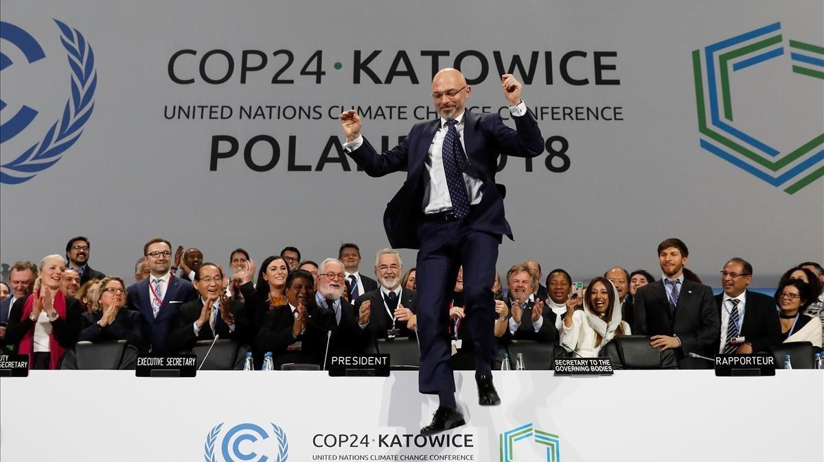 El ministro polaco de Medio Ambiente y presidente de la cumbre, Mychal Kutyka, da un salto tras sellarse el acuerdo en Katowice.