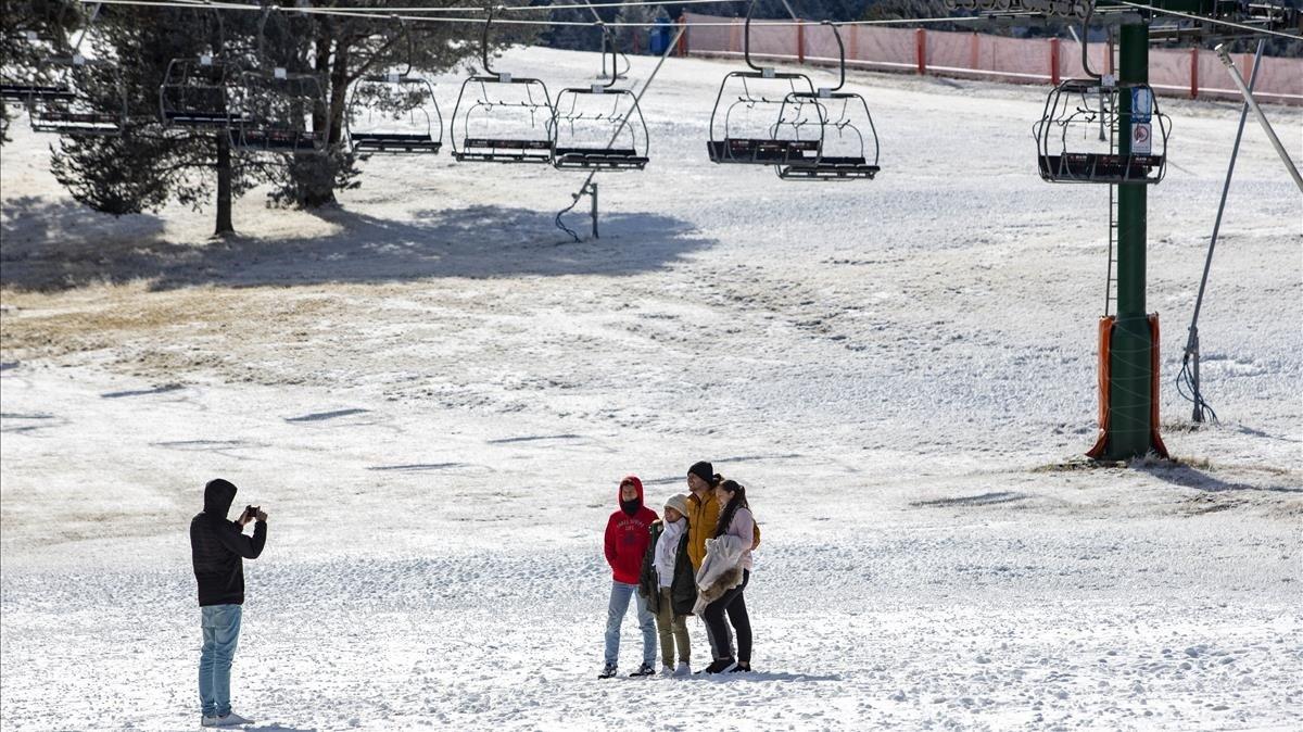 Unos jóvenes se fotografían en la pista Llarga de la Molina, tras la caída de una nevada, el pasado jueves.