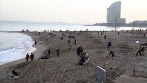 Algunos voluntarios recogen desperdicios en la playa de la Barceloneta, ayer, entre curiosos que se han acercado a ver los efectos del temporal.