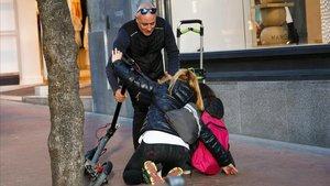 Un señor asiste a una mujer y su hija tras caerde un patinete eléctrico en la acera, el pasado jueves en Terrassa.