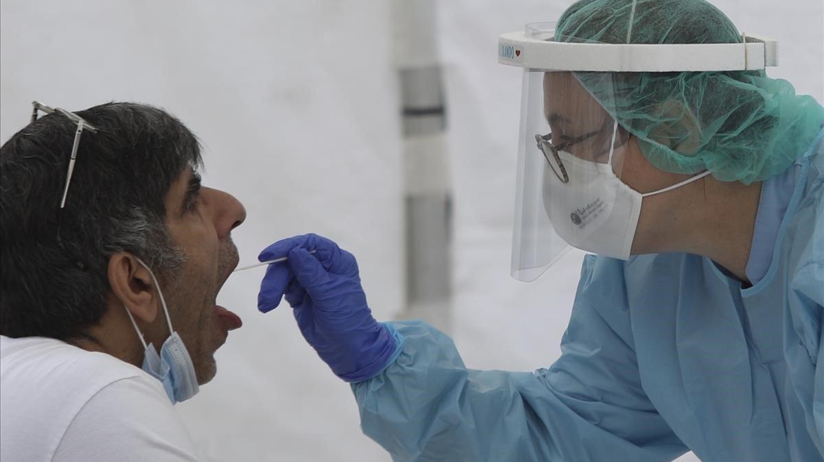 Un sanitario realizando una prueba del covid a una paciente.