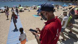 Un agente cívico controla el aforo en la playa de Llafranc, en Palafrugell, este sábado al mediodía.