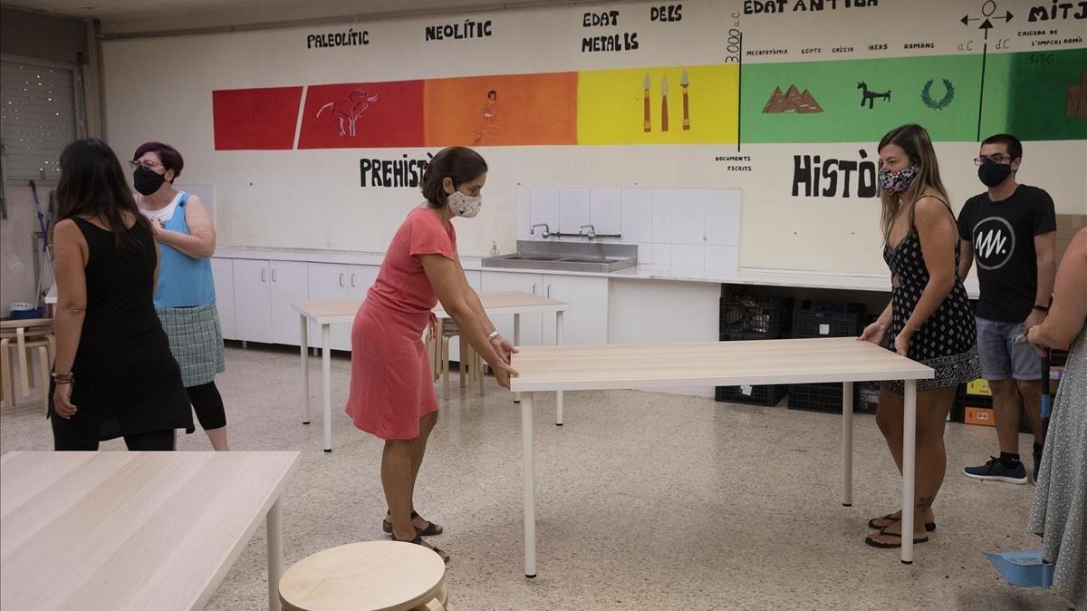 Profesoras del colegio Lluís Millet de Santa Coloma de Gramenet recolocan el mobiliario de un aula, el viernes pasado.