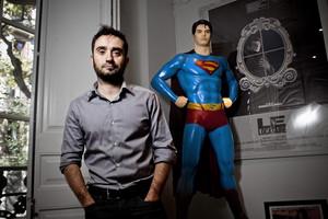 J. A. Bayona junto a una imagen de Supermán, un héroe habitual en sus vídeos musicales.