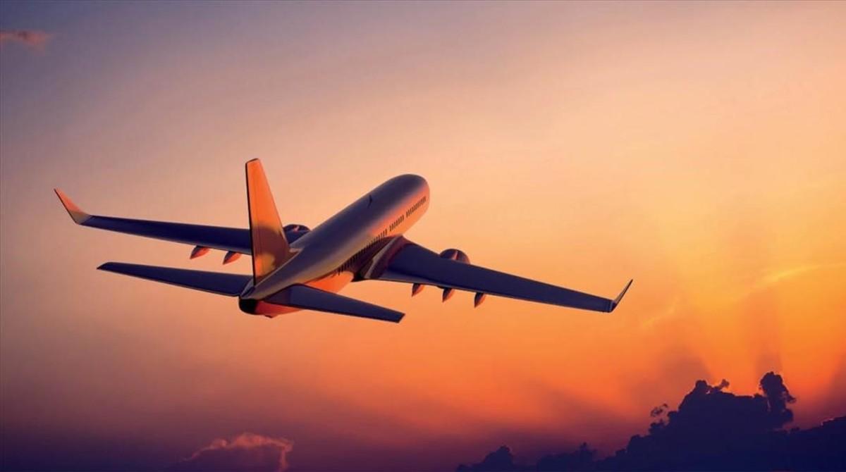 Un avión despega de un aeropuerto al atardecer.