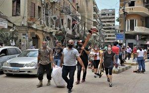 Voluntarios limpian las calles y las edificaciones destrozadas por la explosión Beirut.