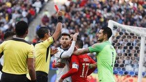 El colegiado muestra la tarjeta roja a Messi y Medel.