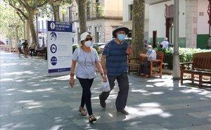 Paseantes con mascarilla por la rambla de Figueres.