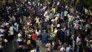 Decenas de migrantes venezolanos esperan en Cali un transporte para regresar a su país debido a la crisis del coronavirus.