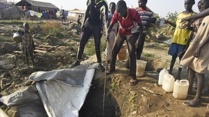 Desplazados por el conflicto civil sacan agua de un pozo en un campo de refugiados de Juba.