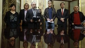 El diputado de Amaiur Rafael Larreina, ante el micrófono, junto a representantes de ERC y el BNG, lee el manifiesto a favor del cierre de la causa de las herriko tabernas. EFE / JUAN CARLOS HIDALGO
