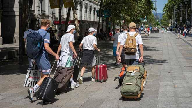 La entrada de turistas en España cae en junio un 97,7%. En la imagen, un grupo de turistas suizos, en Portal de l'Àngel, camino del aeropuerto.