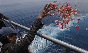 Un familiar de una de las víctimas del accidente del avión de Lion Air lanza flores en las proximidades del lugar donde se produjo el siniestro, en Indonesia.