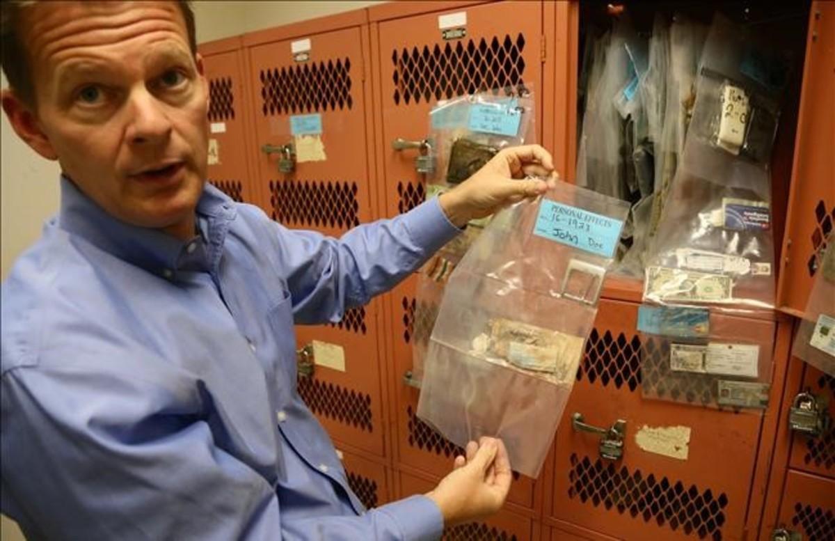 El forense Gregory Hess muestra los efectos personales que llevaban los inmigrantes fallecidos.