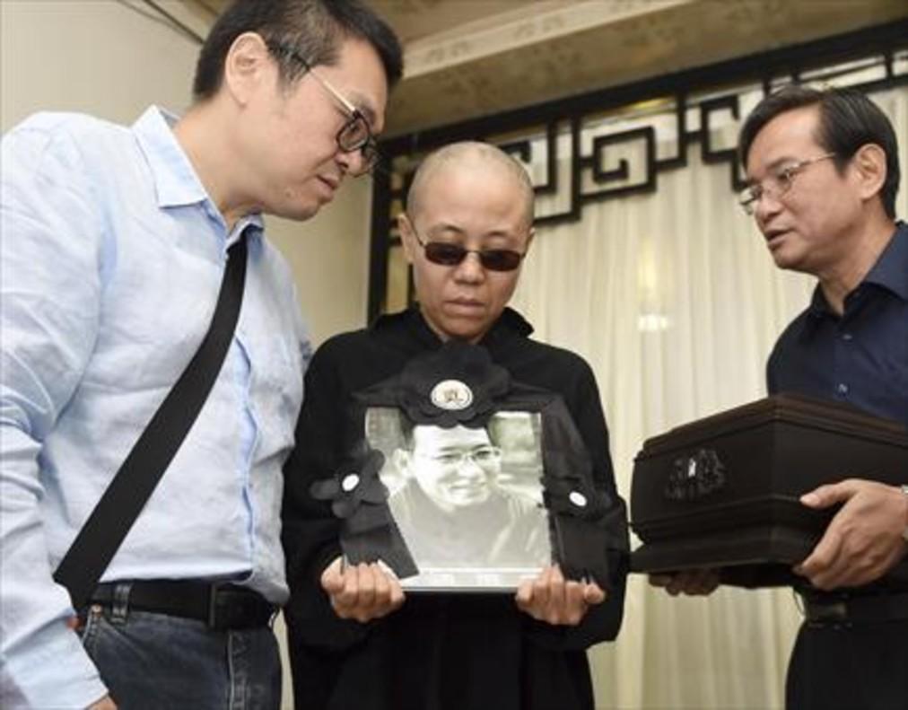 Liu Xia, con una foto y las cenizas de su marido, Liu Xiaobo, el día del funeral.