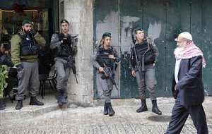 Un hombre palestino pasa junto a soldados en la ciudad vieja de Jerusalén.