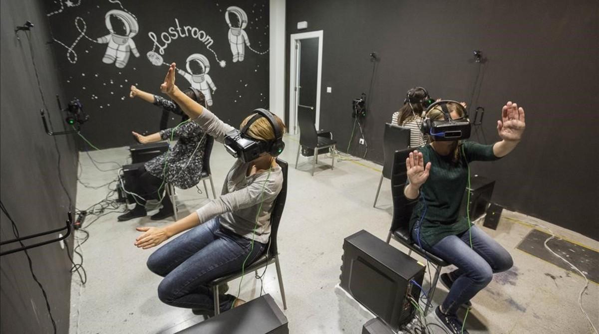 Cuatro jugadoras de Cosmos, el escape room virtual deLostroom, intentan volar sin despegar los pies del suelo. Lo que ellas estánviendo: que son una pandade cyborgs en una estación espacial.