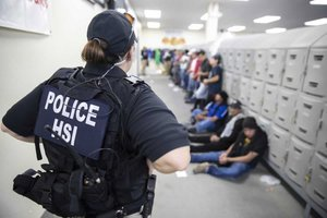 Agentes migratorios de los EEUU custodian a los detenidos en la redada de Misisipi.EFE