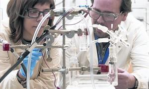 Investigadores 8Marta Blasco y Álvaro Reyes, ante el prototipo del catalizador de hidrógeno.