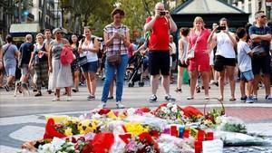 Flores, velas y otros objetos sobre el mosaico de Miró, en La Rambla, en recuerdo de las víctimas del atentado.