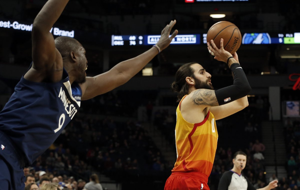 Minnesota Timberwolves' Luol Deng, left, looms in as Utah Jazz's Ricky Rubio, of Spain, shoots in the first half of an NBA basketball game Sunday, Jan. 27, 2019, in Minneapolis. (AP Photo/Jim Mone)