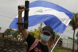 Un joven manifestante alza su arma artesanal y la bandera nacional de Nicaragua contra el régimen de Ortega.