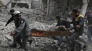 Miembros de Defensa Civil Siria evacuan civiles heridos tras un ataque aéreo a Saqba, en Guta oriental