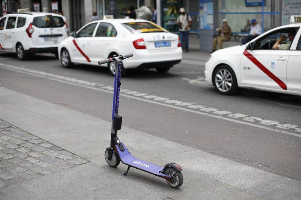 Un patinete eléctrico aparcado frente a unos taxis en las inmediaciones de la Puerta del Sol de Madrid.