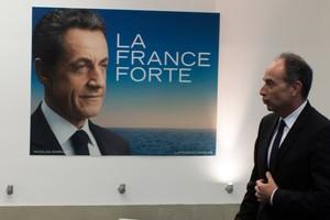 El presidente de la UMP, Jean-François Cope, pasa delante de un cartel con la imagen de Nicolas Sarkozy, en la sede del partido conservador, el pasado día 8 en París.