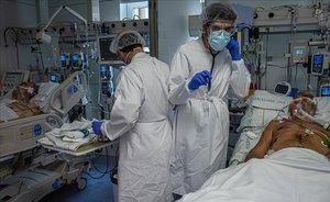 Sanitarios atienden a un enfermo de covid en la uci del Hospital Clínic.