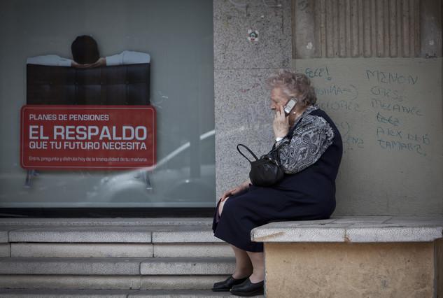 Una dona gran parla per telèfon mòbil al costat d'un cartell de plans de pensions.