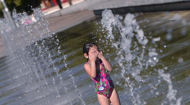 Una niña se refresca en una de las fuentes de Córdoba.