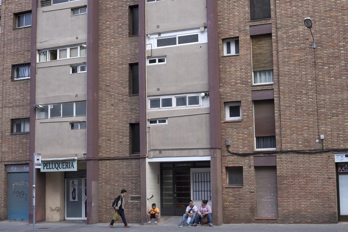 Viajeros que esperan el bus usan el portal numero 34 de la calle Sant Adrià como banco