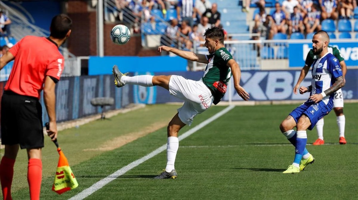 Dídac Vilà intenta controlar un balón ante la mirada de Aleix Vidal.
