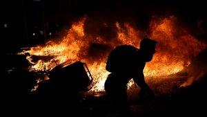 Un manifestante independentista junto a una barricada en llamas, la noche de este martes en el centro de Barcelona.