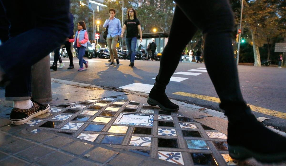 Peatones pasan junto a la obra de Ememem en la plaza de Urquinaona.