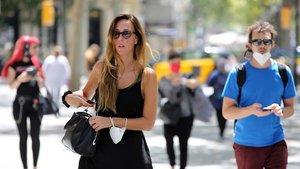 Una mujer pasea por Barcelona con la mascarilla colgada del brazo. A su lado, un hombre lleva su tapabocas bajado a la altura de la barbilla.