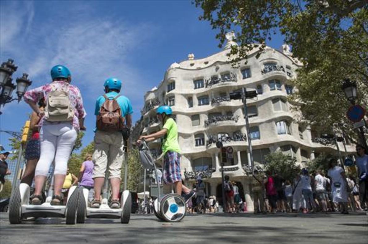 Turistas sobre segways frente a La Pedrera, en Barcelona.