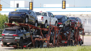 Un camión transporta coches del grupo FCA en la planta de Detroit.