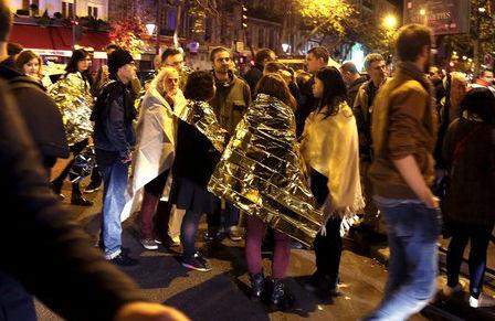 Las personas secalientan bajo mantas térmicas de protección tras ser liberados dela sala de conciertos.