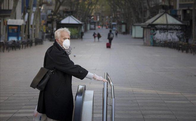 Una mujer con mascarilla en la Rambla de Barcelona, vacía.