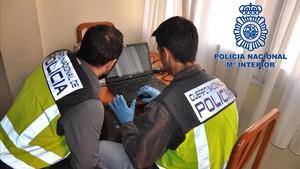 Dos agentes de la Policía Nacional inspeccionan un ordenador con material pornográfico.