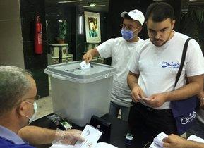 Dos hombres, en una mesa electoral, este domingo en Damasco.