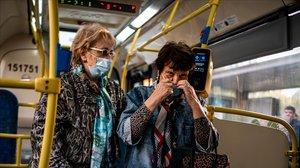 Dos mujeres con mascarilla en el transporte público de Moscú.